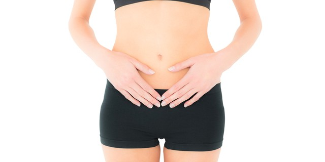 Closeup mid section of a fit young woman with stomach pain over white background