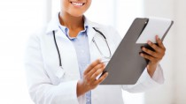 healthcare and medical concept - smiling african female doctor with prescription in hospital