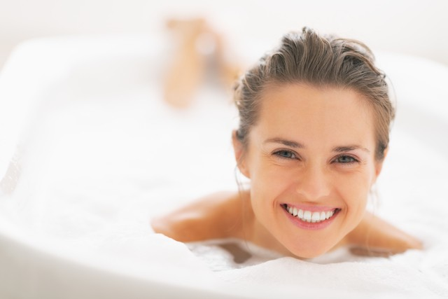 Portrait of smiling young woman laying in bathtub