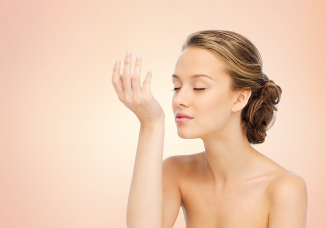 beauty, aroma, people and body care concept - young woman smelling perfume from wrist of her hand over beige background