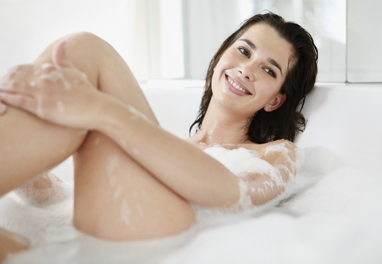 Relaxed Caucasian female enjoys bubble bath while looking away